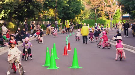 секунды : tokyo, japan - november 17 2019: Static video of some japanese  parents watching over children wearing helmets practicing bicycles on training bikes in Tokyo. Стоковые видеозаписи