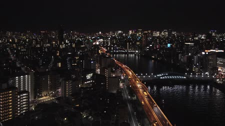 high angle night video of the Sumida river and the tokyo highway in the district of Asakusa Japan.