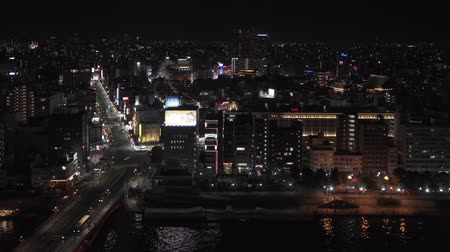Tokyo, Japan - March 01 2020: high angle night static video of the Sumida river and the Sensoji Temple in the district of Asakusa, Tokyo, Japan.