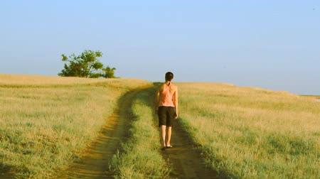 поход : Girl walking on empty rural road far away in summer day