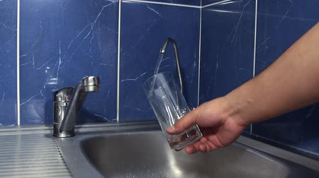 woda mineralna : The person pours water from the filter in a glass with ice