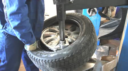 szerelő : Mechanic removes car tire closeup Stock mozgókép