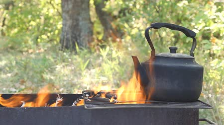 fogão : Black old smoked teapot on the campfire