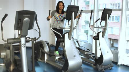 elliptical : young woman doing exercise on a elliptical trainer