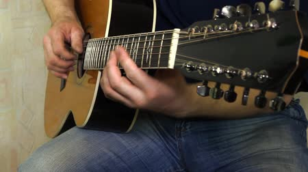 gitáros : performer playing on the acoustic guitar. Musical instrument with guitarist hands