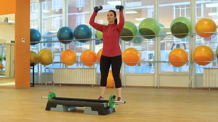 сильный : Young woman doing exercise with dumbbells