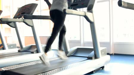 kardiyoloji : People at the gym exercising. Run on a machine. Out of focus Stok Video