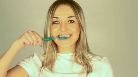 зубы : healthy young woman brushing teeth in bathroom
