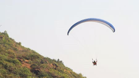 kaide : Goa India  February 22 2015: Paragliding over the mountains against clear blue sky. Extreme sport.