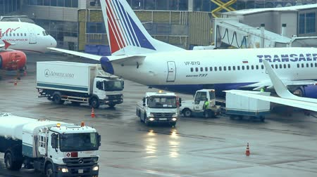 авиация : Moscow, Russian Federation  February 20, 2015: Airport traffic: landing airplanes, waiting for takeoff permission aircrafts on runway, loading and unloading luggage.