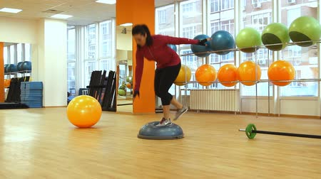 eğitici : Rostov on Don, Russian Federation  January 05, 2014: Young woman doing fitness exercise with bosu ball.