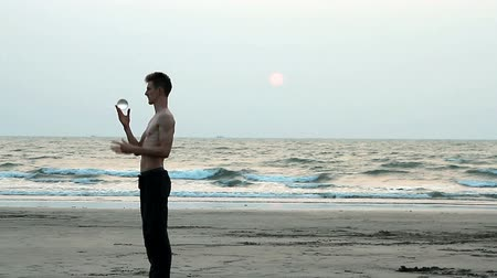 arambol : Goa, India – February 10, 2016: Unidentified man juggling with glass ball on the beach