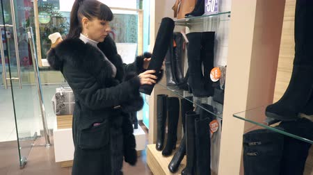 bota : Volgograd, Russian Federation – January 26, 2017: Young girl chooses in the boutique winter boots Stock Footage
