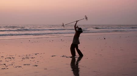 frick : Goa, India - February 23, 2016: Unidentified man spinning pole on the beach.