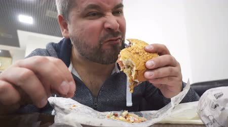 morder : Hungry man eating big hamburger in fast food cafe Stock Footage
