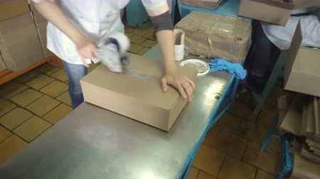 paketleme : Woman hands holding packing machine and sealing cardboard boxes with adgesive tape Stok Video