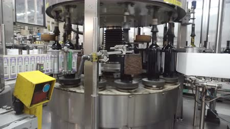 fiscal : Machine applying excise stamps for wine products at a distillery. Bottling and sealing conveyor line at winery factory.