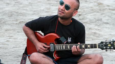 arambol : Goa, India - February 27, 2016: Unidentified man playing music on the beach. Stock Footage