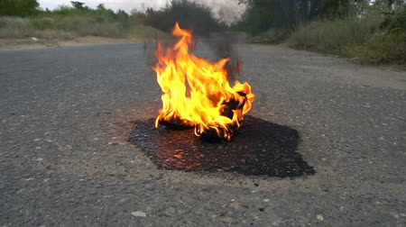 high heel shoe : A pair of female shoes in fire on an empty road