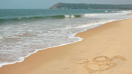 coração : Waves touch sand with the inscription I love