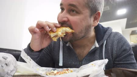 munch : Hungry man eating big hamburger in fast food cafe Stock Footage