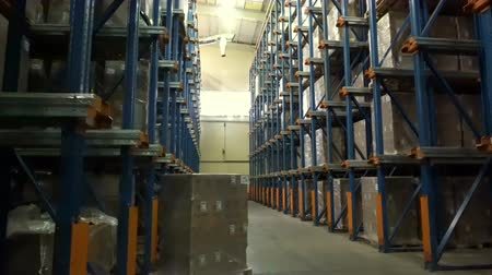 stockpile : Work of loaders on loading pallets with cardboard boxes on racks in a modern warehouse