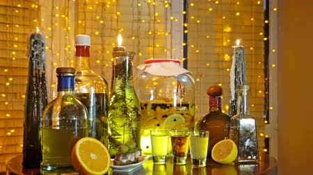 tinctures : The range of alcoholic tinctures in the bar on the table near the window with blinds and a garland Stock Footage