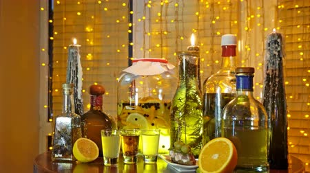 tincture : The range of alcoholic tinctures in the bar on the table near the window with blinds and a garland Stock Footage
