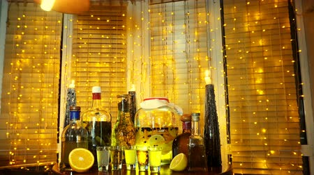 виски : The range of alcoholic tinctures in the bar on the table near the window with blinds and a garland Стоковые видеозаписи