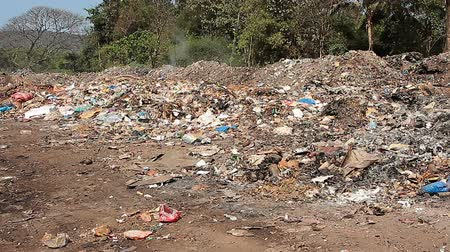 stacks : Large garbage dump waste with smoke at sunny day