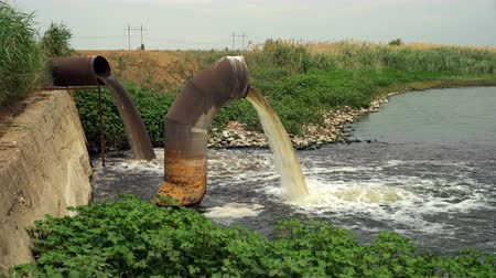 gushing : Wastewater from two large rusty pipes merge into the river in clouds of steam