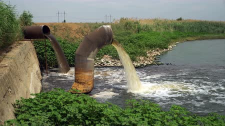 waste water : Wastewater from two large rusty pipes merge into the river in clouds of steam