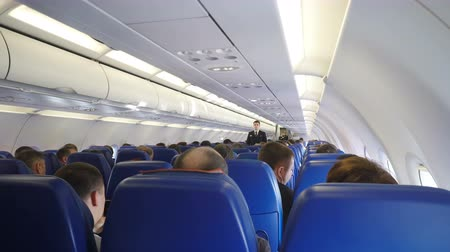 lugares sentados : Moscow, Russian Federation – March 16, 2017: Interior of airplane with passengers on seats and steward conducts safety training after takeoff.