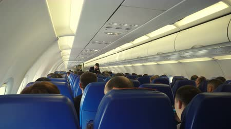 steward : Moscow, Russian Federation – March 16, 2017: Interior of airplane with passengers on seats and steward conducts safety training after takeoff.