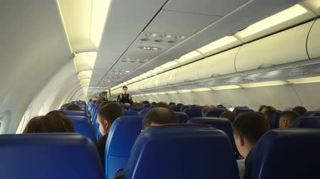 бортовой : Moscow, Russian Federation – March 16, 2017: Interior of airplane with passengers on seats and steward conducts safety training after takeoff.