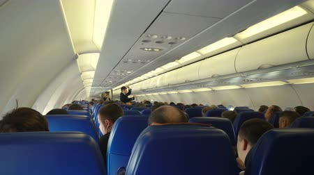 фюзеляж : Moscow, Russian Federation – March 16, 2017: Interior of airplane with passengers on seats and steward conducts safety training after takeoff.