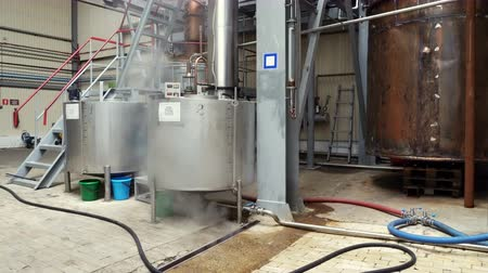 distillation : Industrial production equipment for the distillation of alcohol, copper tanks and steam around them