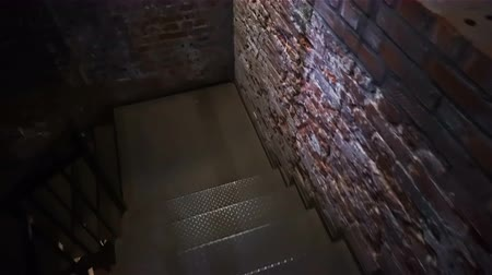 catacomb : Descent to the basement with brick walls on a metal staircase