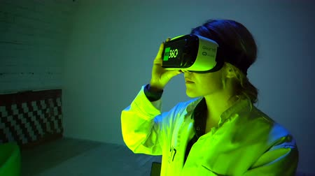 Moscow, Russian Federation – March 17, 2017: Girl scientist performs modulation using virtual reality glasses in a dark room.