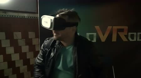 Moscow, Russian Federation – March 17, 2017: Man using virtual reality glasses in a dark room.