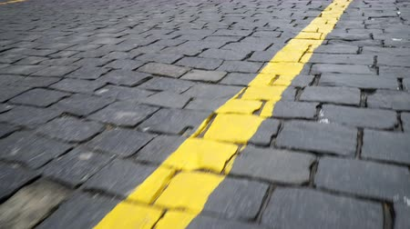pista de corrida : Yellow line on a road paved with black stone blocks
