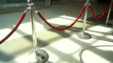 porta de entrada : Silver metal stanchions with red velvet rope for VIP access