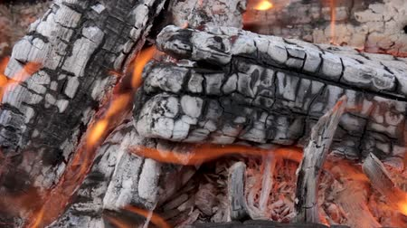 Hot coals from burning wood log and firewood in a campfire with smoke and flame.