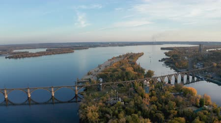 Aerial view from drone on railway bridge above Monastic island and Dnieper river in Dnipro city. Autumn landscape and cityscape background. (Dnepr, Dnepropetrovsk, Dnipropetrovsk)