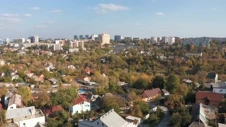 Panoramic aerial view of autumn cityscape from the drone. Urban trees against skyline background.
