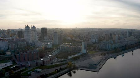 Aerial top view from drone on downtown area of Dnipro city. Flying over Dnieper river and buildings at sunset. Cityscape and skyline at autumn evening.