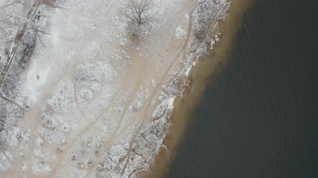 Video footage of flying over shore of Monastic island with snow on the ground in the middle of the Dnieper river at winter time. Aerial view from the drone.
