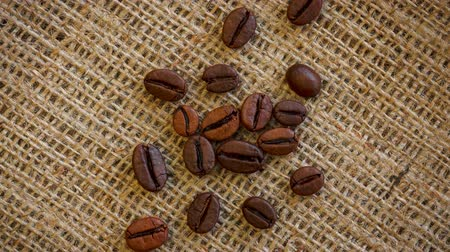 Natural brown roasted coffee beans on burlap texture. Seamless loop rotating background. Vídeos