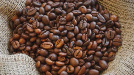 Natural brown roasted coffee beans on burlap texture. Seamless rotating background.