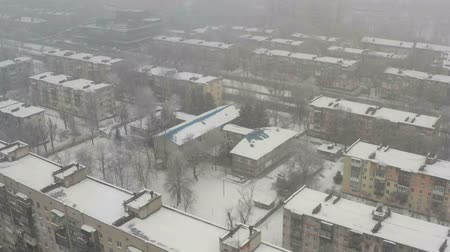 Fly over roof of building covered with snow. Winter foggy cityscape background.